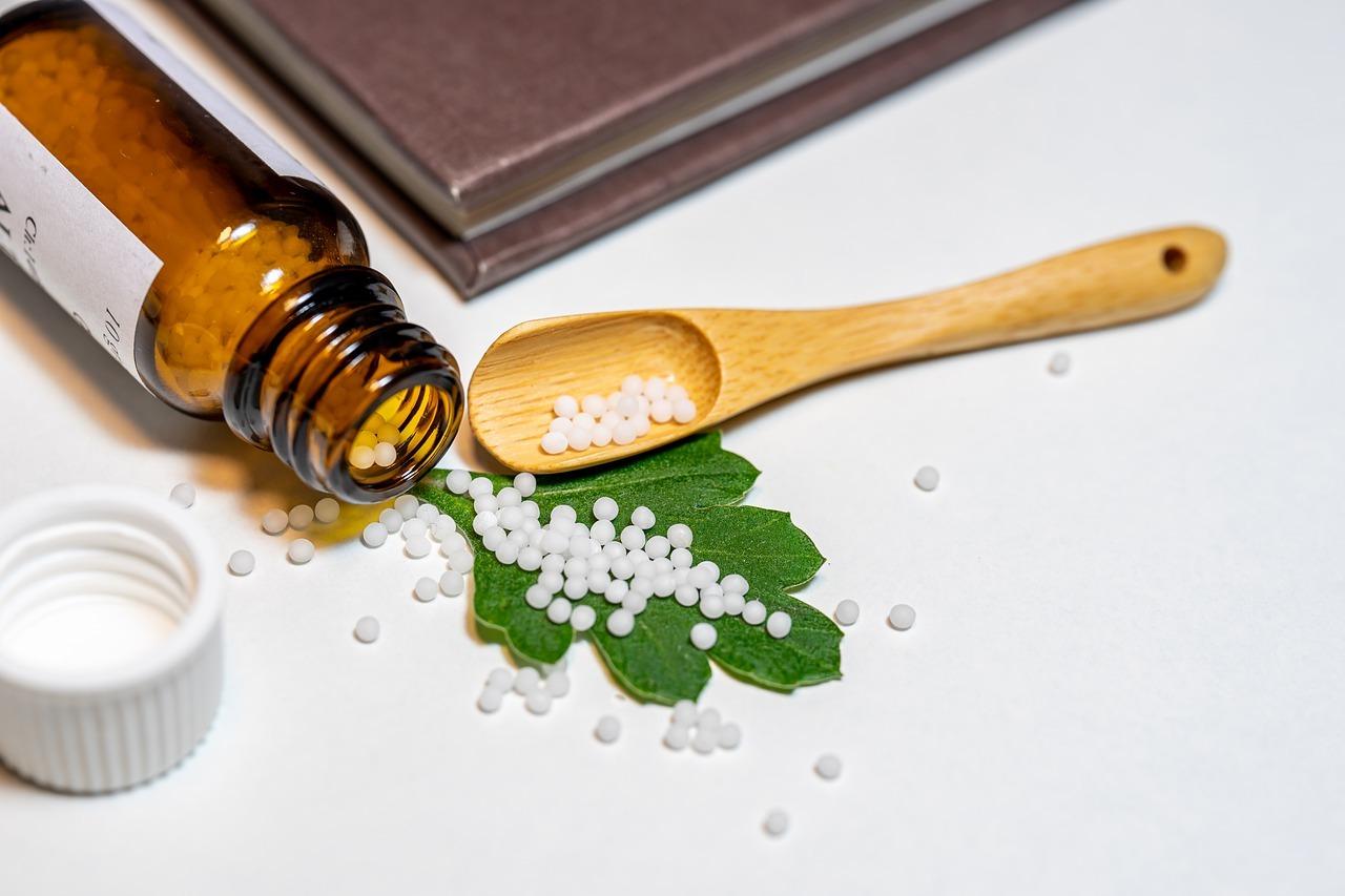 Brun veltet glass med homeopatiske kuler som ruller ut og over et grønt blad og i en trefarget skje