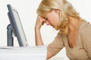 sliten dame hviler hodet i hånden foran pc skjermen