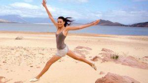 Mørkhåret kvinne frisk og energetisk på en strand