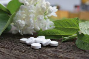 Hvite tabletter på en sort sten med hvite blomster og grønne blad bak