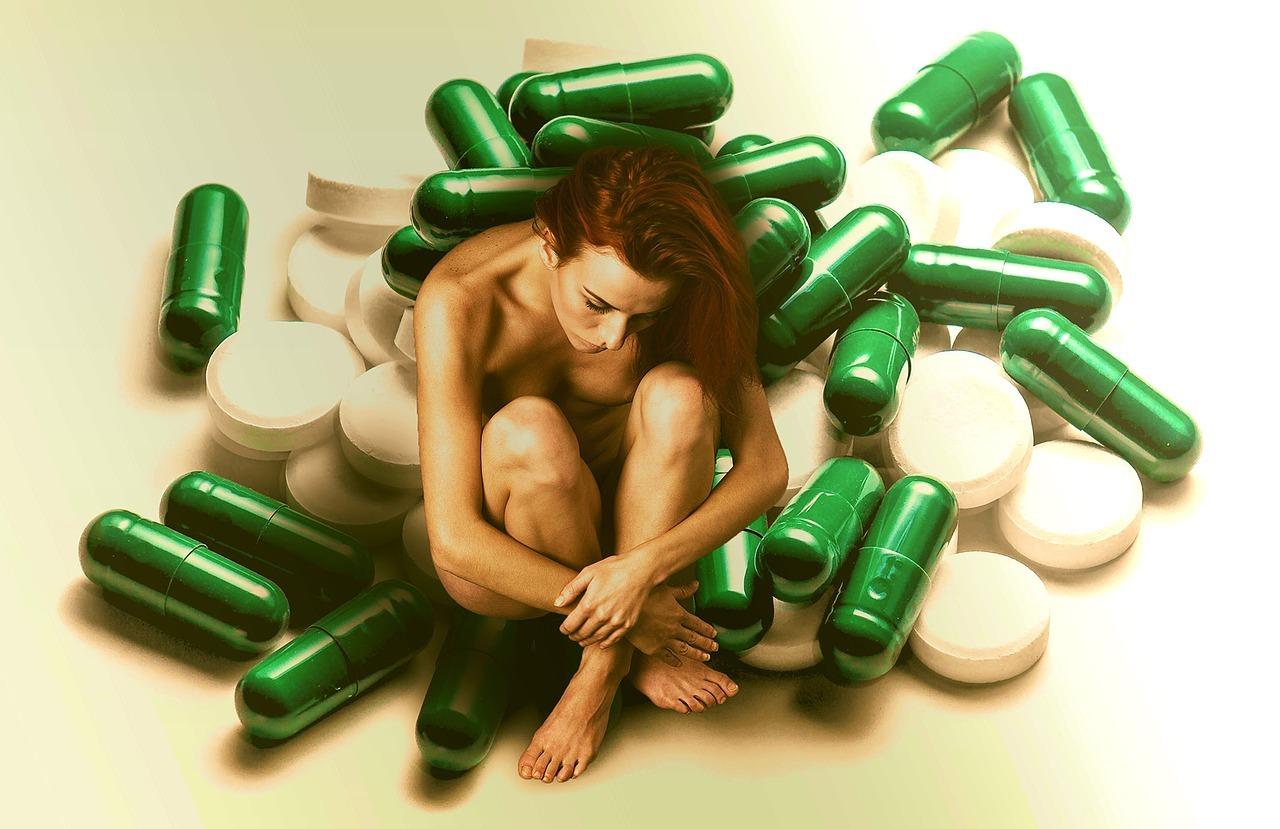 En naken kvinne sitter i en haug grønne og hvite piller