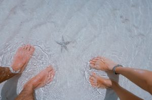 herreføtter og dameføtter på sand og under vann