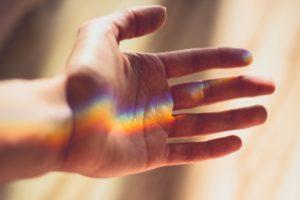 hånd som det lyser en regnbue inn i