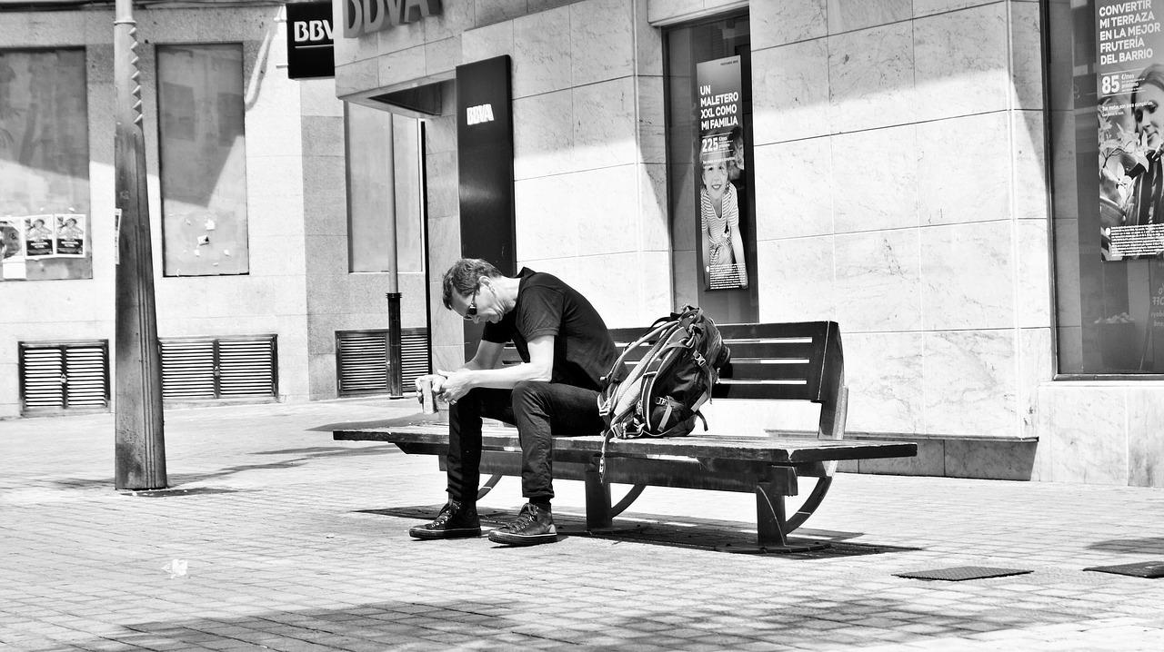 sort hvitt bilde sliten mann på benk