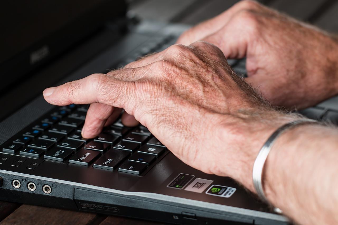 Hender hos eldre mann som skriver på et tastatur